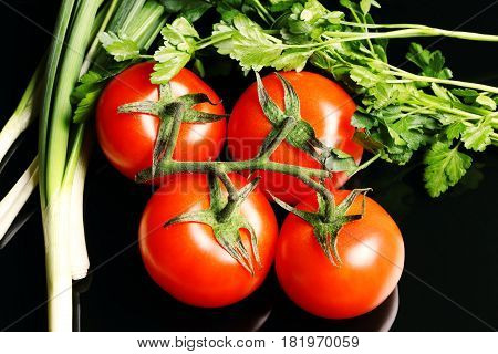Red tomatoes with parsley and onions isolated on a black background