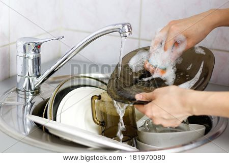 Human Hand Dishwashing Sponge Foaming Or Pouring Water On The Glass