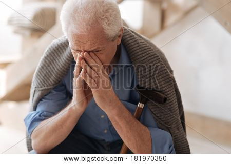 So many emotions. Gloomy cheerless elderly man sitting with a walking stick and crying while not being able to hold his emotions