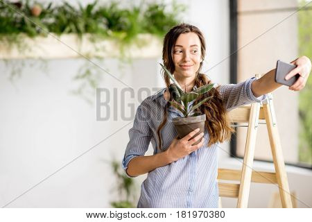Woman making selfie photo standing with flowerpot on the ladder at home