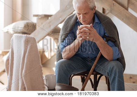 Being all alone. Unhappy retired senior man sitting on the chair and having tea while looking at the empty space near him
