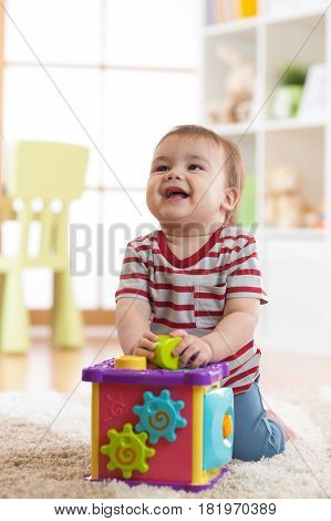 Baby toddler boy playing indoors with sorter toy sitting on soft carpet