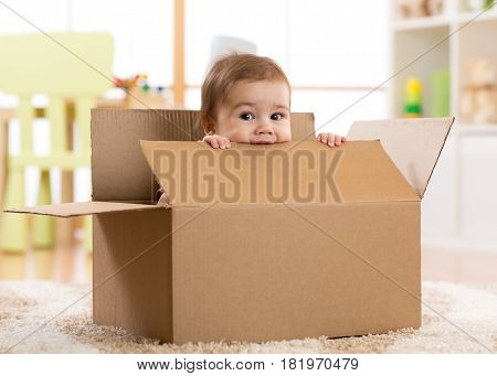 pretty baby infant boy sitting inside a box