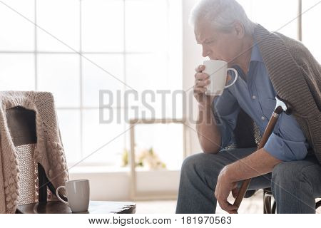 In despair. Desperate depressed aged man looking at the empty chair and missing his wife while pretending to drink tea with her