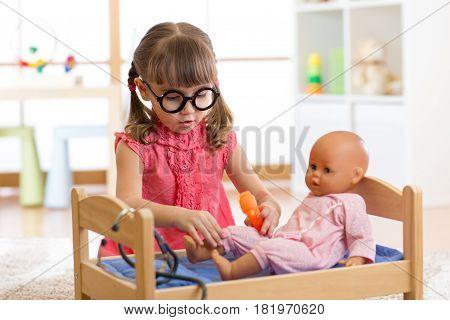 Child kid in kindergarten or nursery school. Little girl playing doctor with doll.