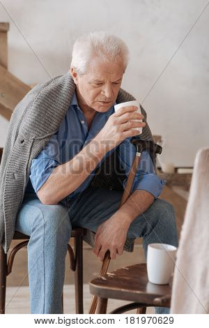 Empty chair. Cheerless unhappy aged man holding a cup and looking at the empty chair while drinking tea