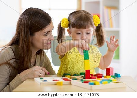 mother and kid daughter playing logical toys at home