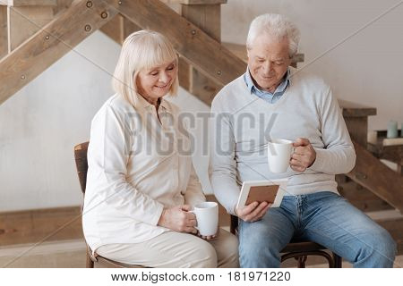 Positive emotions. Cheerful delighted elderly couple looking at the photo and smiling while having tea together