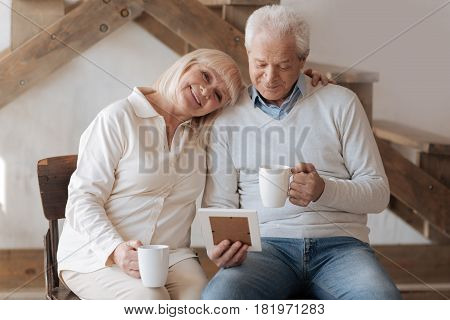 Elderly couple. Cheerful delighted positive woman hugging her husband and smiling while sitting next to him