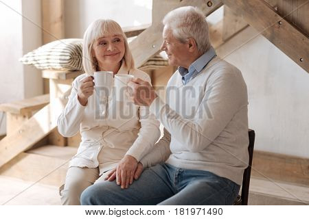 Our favourite tea. Happy aged nice couple smiling and holding cups while drinking tea together