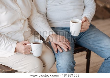 Always together. Close up of a nice loyal elderly couple sitting together and holding hands while having tea