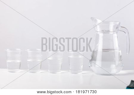 glass jug with water and plastic cups isolated on light grey background