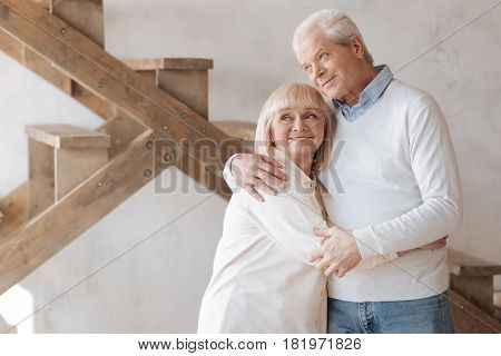 Absolutely happy. Good looking cheerful happy couple standing together and smiling while hugging each other