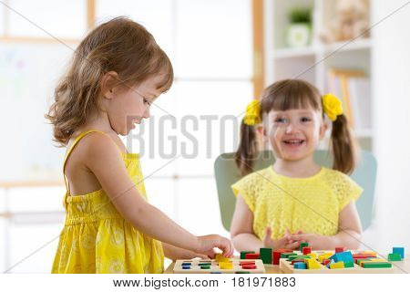 Kids girls playing with logical toy on desk in nursery room or kindergarten. Children arranging and sorting shapes colors and sizes.
