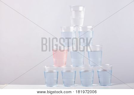 plastic cups piramide with blue water isolated on light grey background. outstanding pink cup, business metaphore, diffenent from others