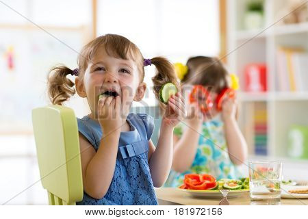 children kids eating vegetables in kindergarten or at home