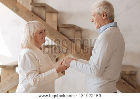 Whole life together. Cheerful delighted elderly couple standing opposite each other and holding hands while smiling poster