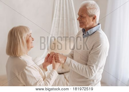 Happy couple. Pleasant handsome senior man looking at his wife and holding her hands while spending time with her