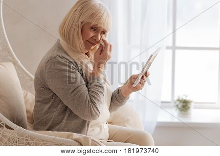 I am so unhappy. Depressed sad aged woman looking at the photograph of her deceased husband and wiping away her tears while crying