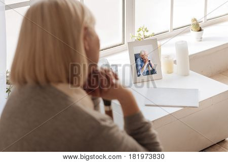 Why did you leave me. Close up of a photo of a deceased husband standing on the bedside table