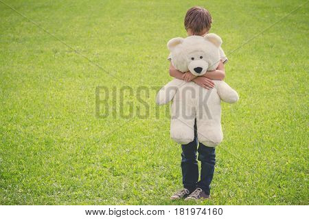Sad boy embracing hid teddy bear. Outdoor.