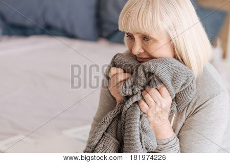 It reminds me of him. Depressed cheerless aged woman holding a knitted jacket and being ready to burst into tears while felling lonely