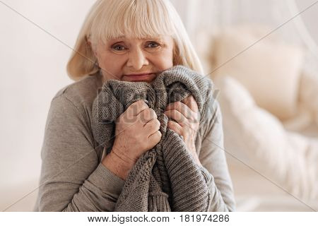 It is so difficult. Depressed unhappy senior woman holding a knitted jacket of her deceased husband and pressing it to her while trying to hold tears