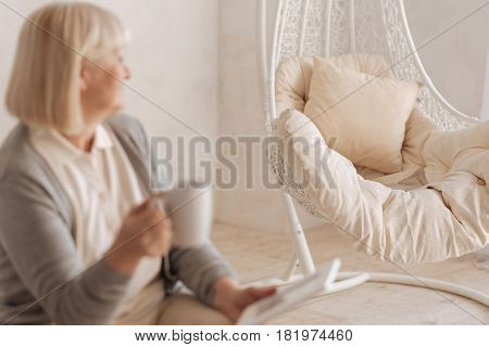 Piece of furniture. Selective focus of an empty armchair standing in the room while being looked at by a nice elderly woman