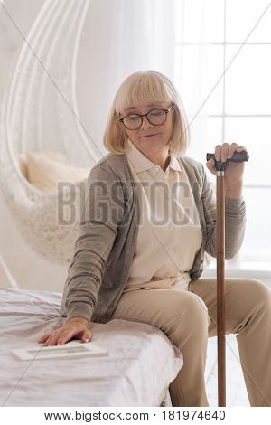 Where are you now. Unhappy cheerless grey haired woman sitting on the bed and looking at the empty space near her while missing her husband
