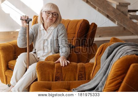 We used to sit here together. Depressed unhappy elderly woman holding a walking stick and looking at the empty space near her while grieving about her husband