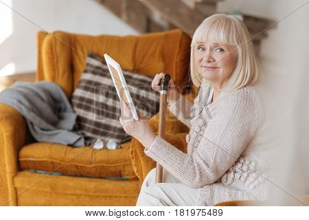 Close person. Nice pleasant aged woman having a photo in her hands and looking at it while sitting in the armchair