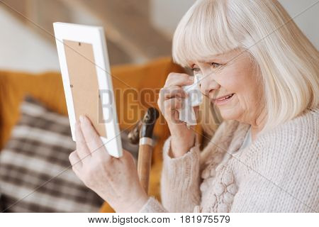 I dont know how to live now. Miserable depressed elderly woman holding a paper tissue and crying while seeing the photo of her husband