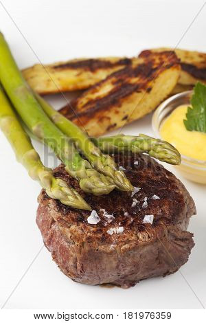 beef steak and asparagus with potatos on a plate