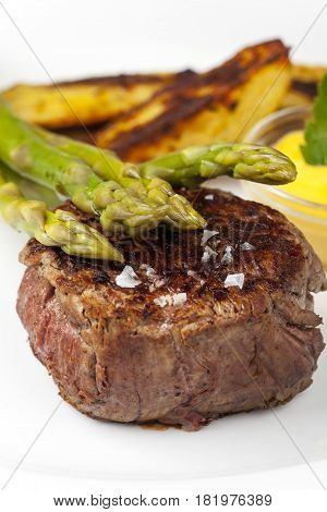 beef steak and asparagus with potatos on white
