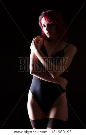 Sexy redhead model in lingerie and leather jacket in studio photo on black background. Erotica and sensuality. Passion and fashion