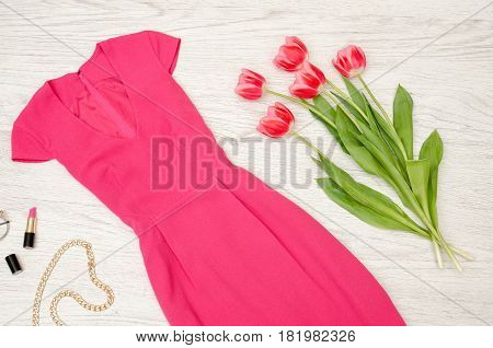 Fashion concept. Crimson dress lipstick and pink tulips. Top view light wood background