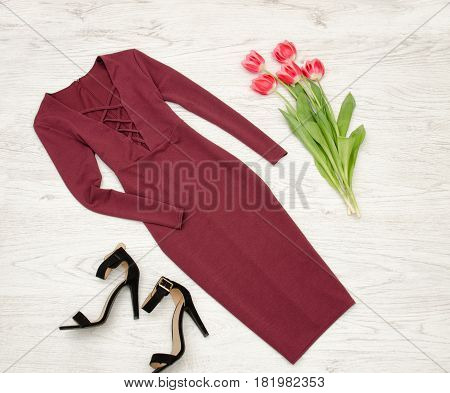 Fashion concept. Burgundy dress black shoes and pink tulips. Top view light wood background