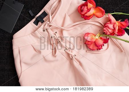 Pink trousers with drawstring on a black background blank tag roses. Fashion concept close-up