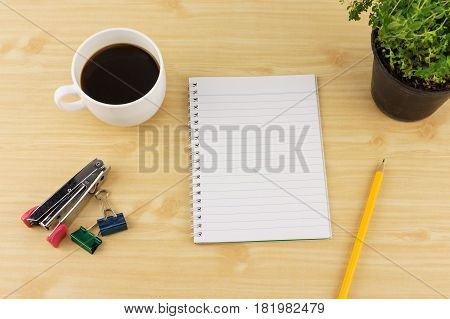 Notebook paper with pencils coffee thyme on flowerpot stapler and paperclip on brown wood table background. Top view with copy space. Concept for website banner background presentation and marketing material.