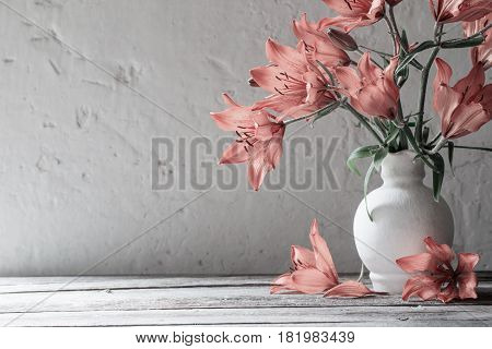orange lily in vase on wooden table
