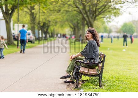 Young woman sitting on bench in summer park.
