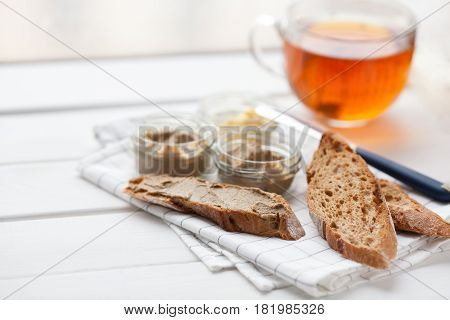 Bread with veal and rabbit pate with butter on a textile background. Copy space.