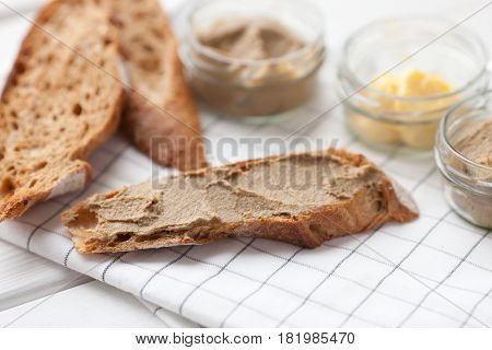 Bread with veal and rabbit pate with butter on a textile background. Top view.