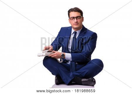 Businessman meditating on the floor isolated on white