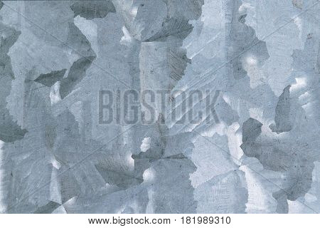 Part of galvanized sheet metal. Visible pattern or design on galvanized metal sheet. Cladding of buildings or fences.