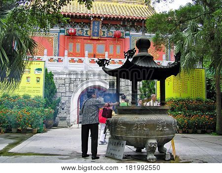 Ngong Ping, Hong Kong - March 24, 2003: An elderly woman lights incense sticks at the entrance of the Po Lin Monastery in Ngong Ping on the island of Lantau in Hong Kong.
