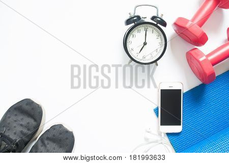 Flat lay of smartphone with sport yoga equipments and clock on white background