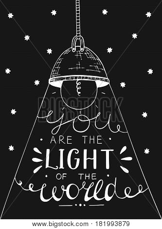 Hand lettering You the light of the world, made on black star background with glowing light bulb. Biblical background. Christian poster. New Testament