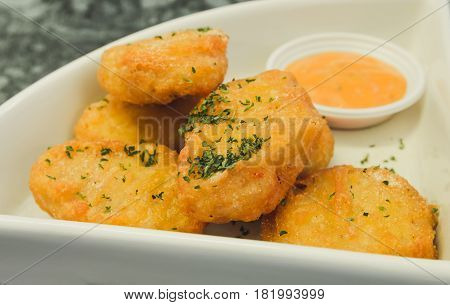 Close up of Crispy chicken nuggets with tomato sauce.