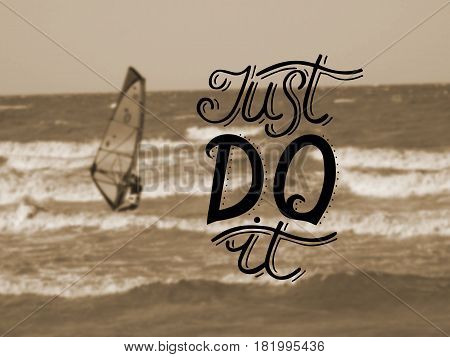 Hand lettering Just do it made on the background of the sea with a floating boat with a sail. Motivational quotes. Poster.